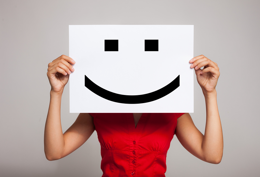 Woman holding a smiling face emoticon
